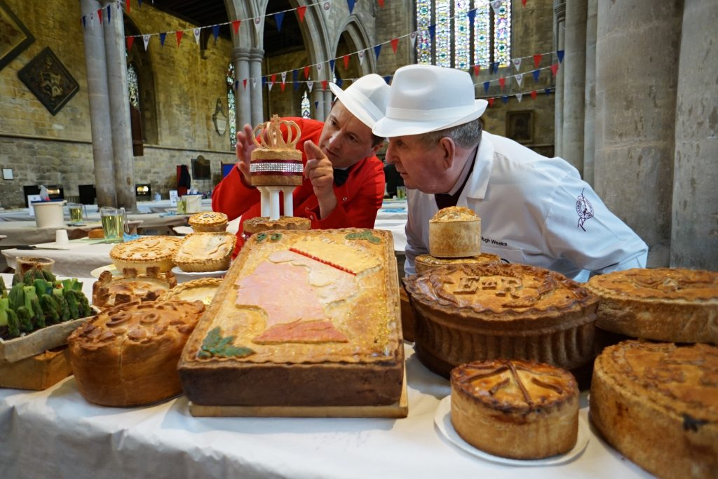 Preparations are underway today (Wednesday 9 March) for the eighth annual British Pie Awards held in Melton Mowbray Church. Deputy head judge Hugh Weeks (right) and one of the event organisers Stephen Hallam (left) inspect the entries for this year's speciality class: 'A pie fit for the Queen's 90th Birthday'. Over 800 pies will be judged today by over 100 judges with results announced on Friday 11th March. Contact Wild Card PR on 01872 243 560 / BPA@wildcard.co.uk for more images or information.